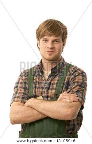 Confident young builder wearing green workwear, standing arms crossed, smiling. Cutout.