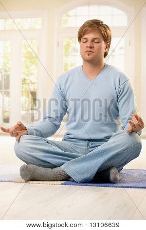 Man sitzt auf dem Boden des Wohnzimmers in Lotus-Haltung, Yoga Meditation Übungen mit geschlossenen Augen.