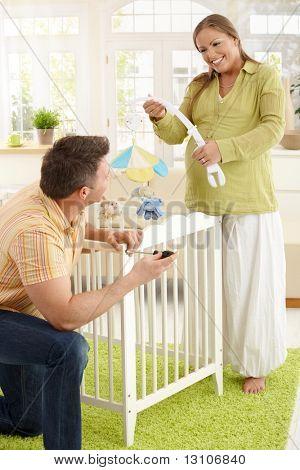 赤ちゃん置くベビー ベッド一緒にリビング ルームに期待して、笑って幸せなカップル。