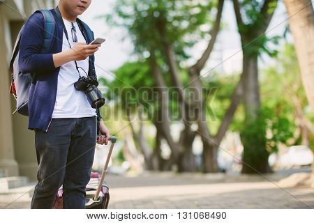 Cropped image of tourist using map in smartphone when standing outdoors