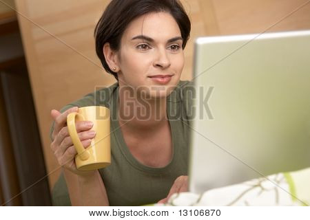 Woman looking at laptop screen smiling, holding coffee mug at home.