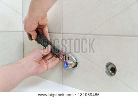 Installing bath faucet. Plumber installs eccentric with an adjustable wrench.