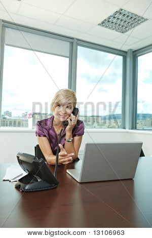 Happy young businesswoman sitting at table in office meeting room, talking on phone, smiling.