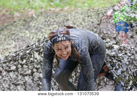 STOCKHOLM SWEDEN - MAY 14 2016: Smiling beautiful woman with braids covered with mudfighting to get out of a camouflage net in the obstacle race Tough Viking Event in Sweden April 14 2016