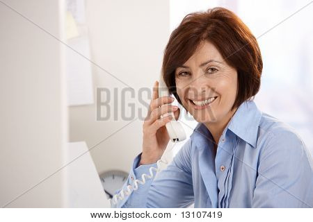 Portrait of smiling senior office worker sitting at desk, using landline phone, looking at camera.