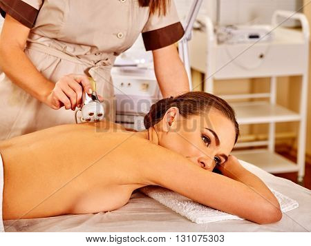 Woman girl lying on her stomach receiving electric back massage on microdermabrasion equipment at beauty salon.
