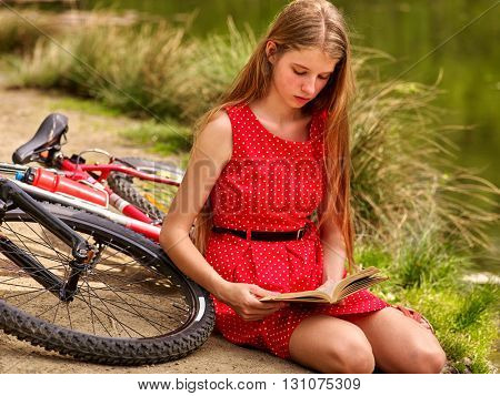 Bikes bicycling girl. Girl wearing red polka dots dress rides bicycle into park. Girl sitting near bicycle read book. Girl sits leaning on bicycle on river shore.