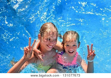 Two children in swimming pool . Children hugging and gesticulate hand victory sign.  Summer holiday.  Outdoor. Girl holding her sister in her arms. Children  activities lifestyle.