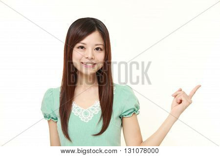 portrait of young Japanese woman presenting and showing something on white background