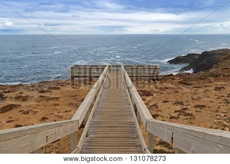 Wooden path and stairs leading to the Blowholes viewpoint overlooking the rough sea at Cape Bridgewater in Victoria, Australia