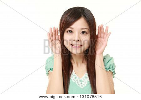young Japanese woman with hand behind ear listening closely