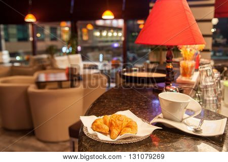 hot croissant and coffee cup at coffeeshop