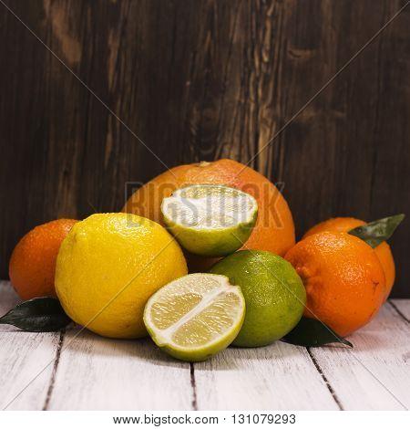 Pile of fresh citrus fruits over wooden background. Lemonade ingredients. Healthy drink concept. Toned image. Selective focus
