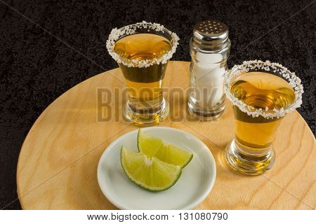 Shots of gold tequila with lime and salt on the round wood board. Tequila shot. Gold Mexican tequila. Tequila