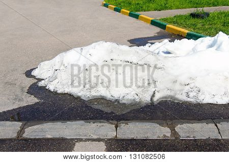 A large pile of dirty and white snow lies on the asphalt road on background green grass
