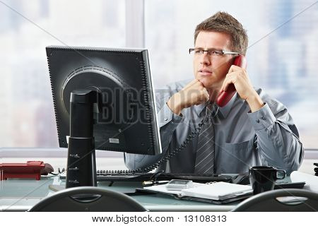 Focused businessman listening to explanation of computer report on landline phone looking at screen sitting in office.?