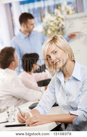 Young businesswoman sitting on business meeting in office making notes, looking at camera smiling.?