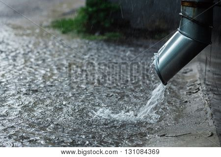Rain water flowing from a metal downspout during a heavy rain. concept of protection against heavy rains. poster