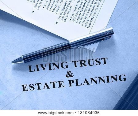 Blue shaded image of living trust and estate planning document. A tax form is also included in the scene.