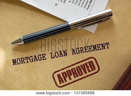 Pen rests on top of a real estate mortgage loan document. A warm color scheme dominates the image.