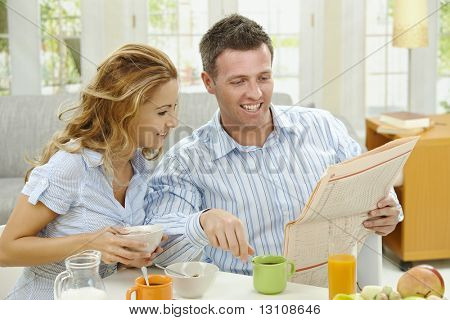Couple having healthy breakfast at home, eating cereals drinking coffee, and reading newspaper.