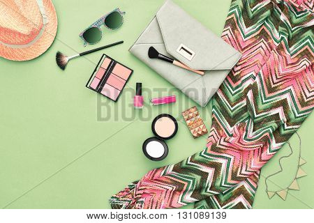 woman essentials. unusual overhead, top view. fashion stylish clothes, cosmetics, makeup accessories set. urban summer girl colorful outfit. stylish handbag clutch, trendy pants, necklace sunglasses.
