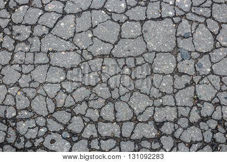 Old worn and cracked asphalt with cracks.