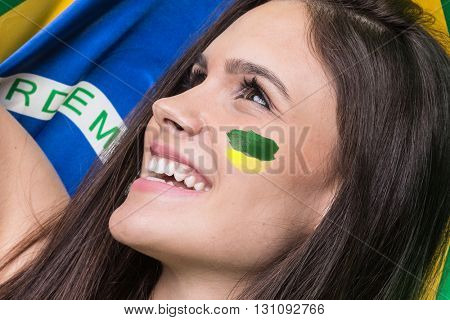 Young brunette fan celebrating with the flag of Brazil