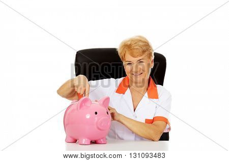 Smile elderly female doctor or nurse sitting behind the desk wit piggybank