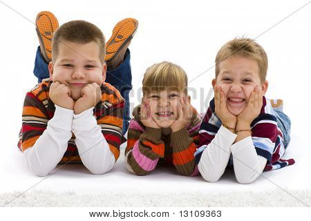 Group of 3 happy children lying on floor, wearing colorful, striped pullover and t-shirt, smiling.  Isolated on white background.