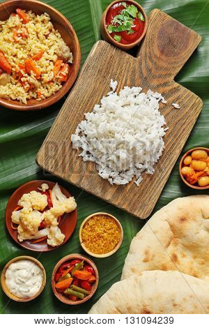 Boiled and fried rice with vegetables, flat bread on banana leaf background