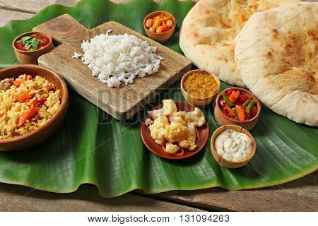 Boiled and fried rice with vegetables, flat bread on banana leaf over wooden background