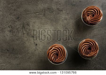 Three chocolate cupcakes on grey background