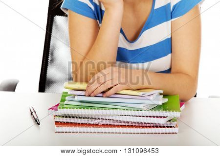 Teenager with huge heap of copybooks