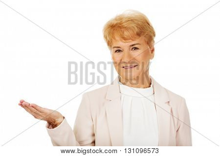 Smile senior woman holding something on open palm