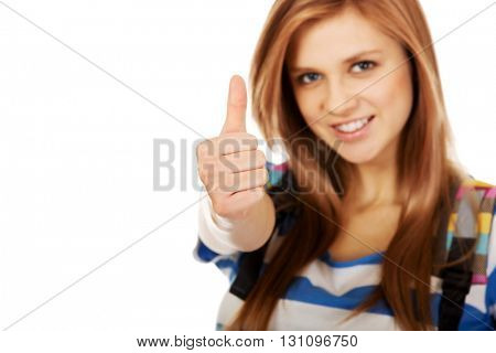 Teenager girl with school backpack and thumb up