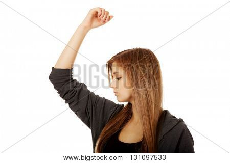 Pretty teen woman sniffing her armpit