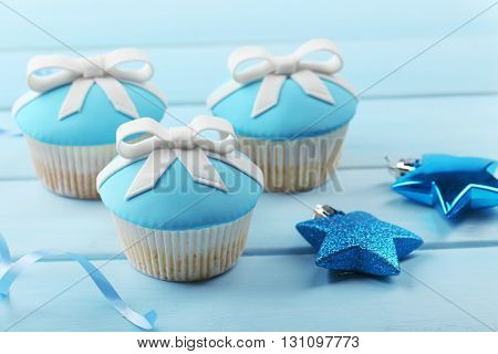Tasty cupcakes with bow and Christmas toys on color wooden background