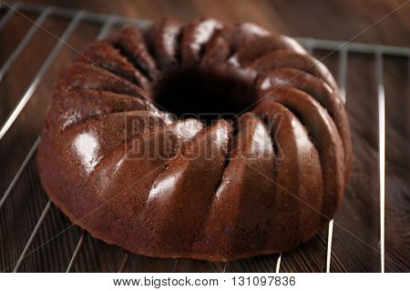 Chocolate cake on metal mat on wooden background