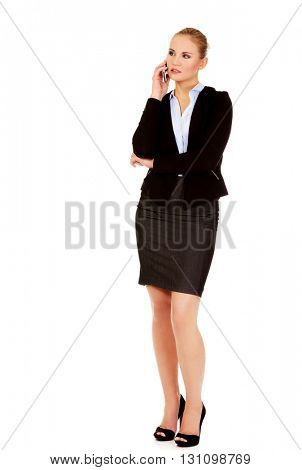 Serious young business woman talking through the phone