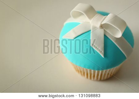 Tasty cupcake with bow on light background