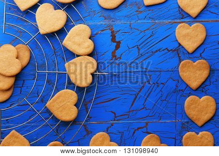 Heart shaped biscuits on metal mat on blue background