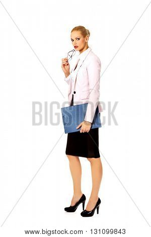Pensive business woman holding a clipboard and glasses