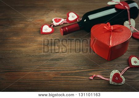 Red wine bottle and gift box on wooden background