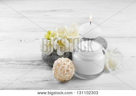 Spa still life with pebbles and cream on wooden background