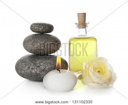 Spa still life with pebbles, oil and candle isolated on white