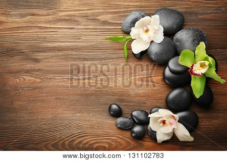 Beautiful spa composition with stones and orchids on wooden background