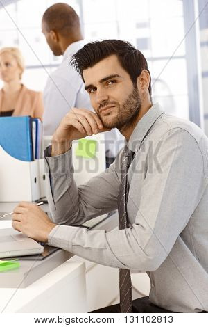 Portrait of young businessman sitting at desk, working, looking at camera.