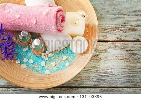 Spa composition with spring flowers in wooden bowl