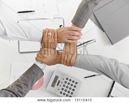 Four hands in unity at businessmeeting in closeup, from high angle view, over table, expressing teamwork.?